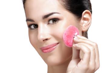 beautiful young woman applying powder foundation