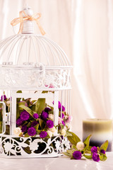 Spa candle in front of white bird cage filled with flowers.