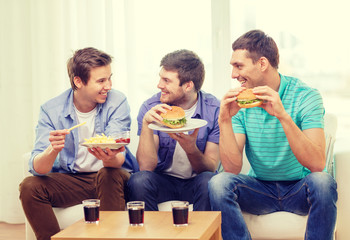 smiling friends with soda and hamburgers at home
