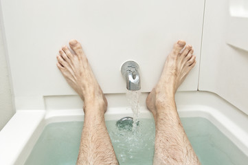 Bathtub With Water Running And Man's Feet