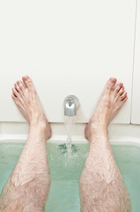 Bathtub Water Running Between Men's Resting Feet