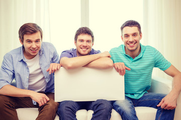 smiling male friends holding white blank board