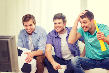 happy male friends with football and vuvuzela