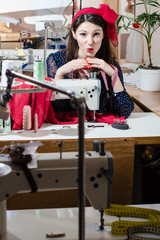 Pretty pinup woman sewing clothes in workshop