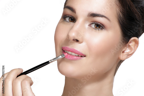 canvas print picture Beautiful young woman applying lipstick with brush