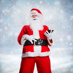 lachender Weihnachtsmann mit Tablet in Winterlandschaft