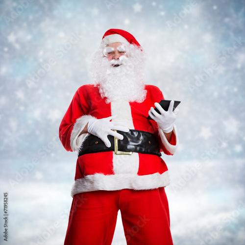 canvas print picture lachender Weihnachtsmann mit Tablet in Winterlandschaft