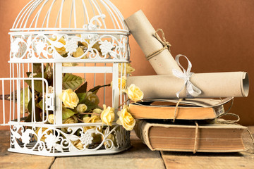 White bird cage ,books and rolled papers