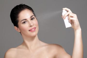 Beautiful woman applying spray water on face