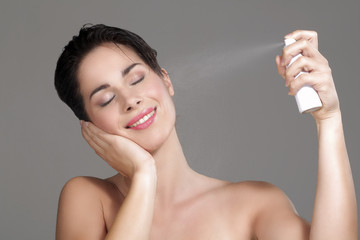 Beautiful woman applying spray water on face