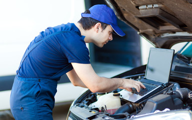Mechanic using a laptop computer to check a car engine