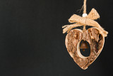 Bark wooden heart on a rope with little opaque brass bell in the poster