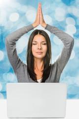 Hübsche Frau meditiert vor einem Laptop Computer