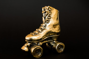 golden roller skate against black background
