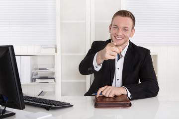 Lachender freundlicher Kundenberater sitzend im Büro