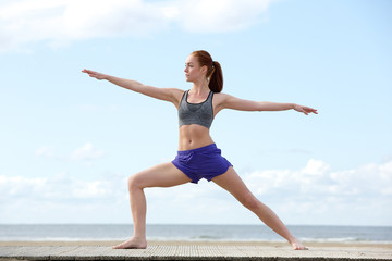 Young woman doing yoga stretch at the beach