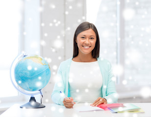 smiling young woman with globe and tablet pc