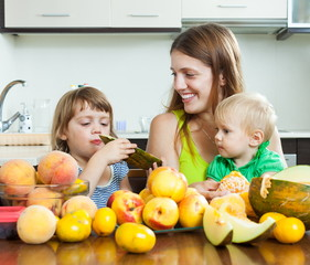 Mother with children eating peaches