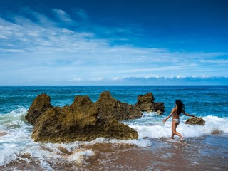 Wellen locken junge Frau ins Meer