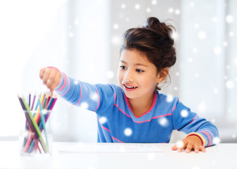 smiling little girl with pencils drawing at home