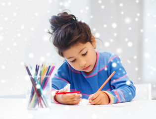 little girl with pencils drawing at home
