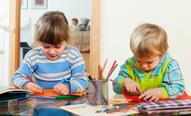 Two  children playing with paper and pencils