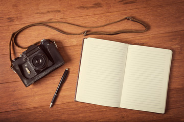 Vintage camera, diary with pan  on wooden table. Instagram style