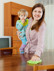 Woman with baby dusting wooden table