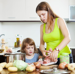 woman with baby cooking with meat