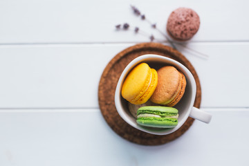 Coloured macarons in cup on white with shallow depth of field