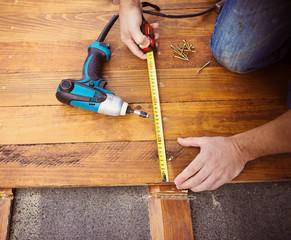 Male hands measuring wooden floor