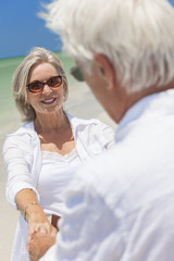 Happy Senior Couple Dancing Holding Hands on Beach