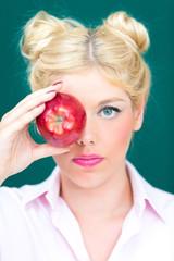 Blonde Frau mit Apfel in der Hand