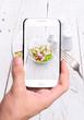 Hands taking photo radish salad with smartphone