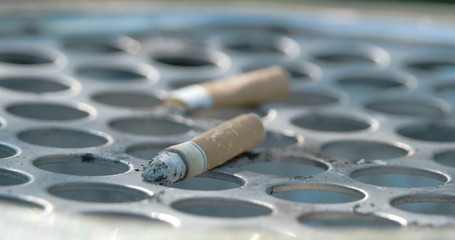 Close up view of the cigarette butt on the bin