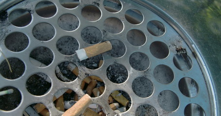 A cigarette bin or ahstray with lots of cigs inside