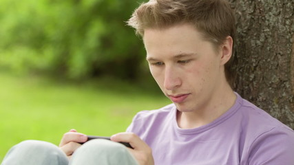 young adult man using smartphone in the park