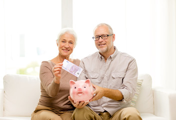 senior couple with money and piggy bank at home