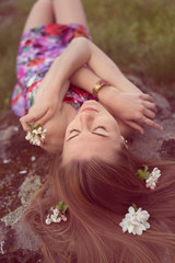 beautiful blonde woman laying on stone with flowers