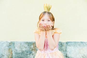 Cute little girl sending a kiss with her hands