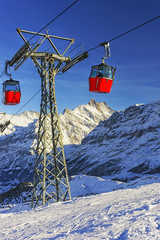 Two red cabins of cable railway on winter sport resort in swiss