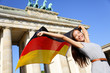 German flag woman happy at Berlin Brandenburg Gate