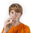 cute boy with orange shirt drinks water