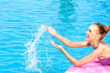 Happy woman splashing water in a swimming pool