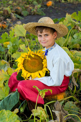 Young happy boy hold sunflower in a garden