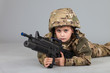 Young boy dressed like a soldier with rifle