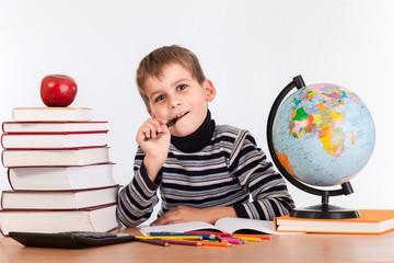 Cute schoolboy is thinking