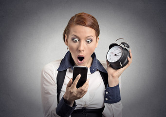 shocked business woman with alarm clock looking at phone