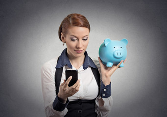woman holding piggy bank looking at smart phone