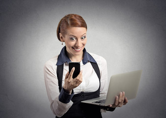 surprised woman reading news on smartphone holding computer